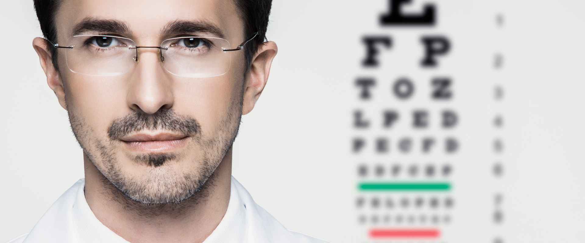 Ophthalmologist with eye chart behind him.